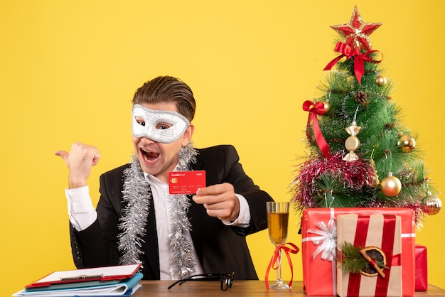 Front view male worker wearing party mask and holding bank card