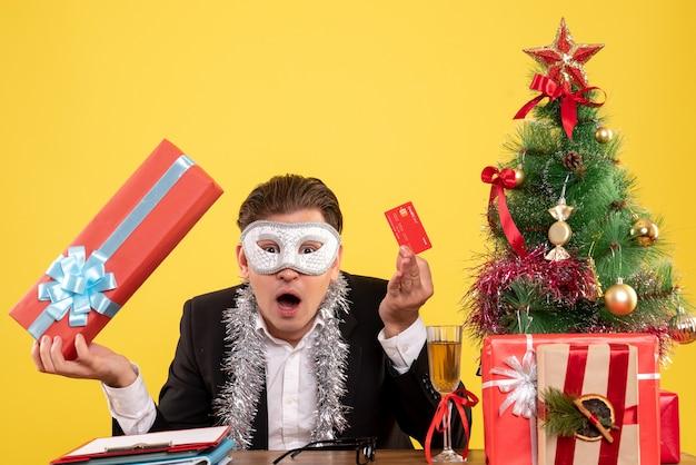 Vista frontale lavoratore di sesso maschile che indossa la maschera del partito e tenendo la carta di credito