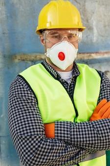 Vista frontale del lavoratore di sesso maschile con occhiali protettivi e giubbotto riflettente