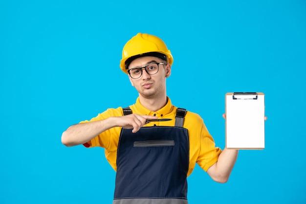 Vista frontale del lavoratore maschio in uniforme gialla sull'azzurro