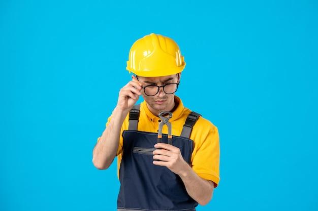 Vista frontale del lavoratore maschio in uniforme gialla che esamina le pinze sull'azzurro