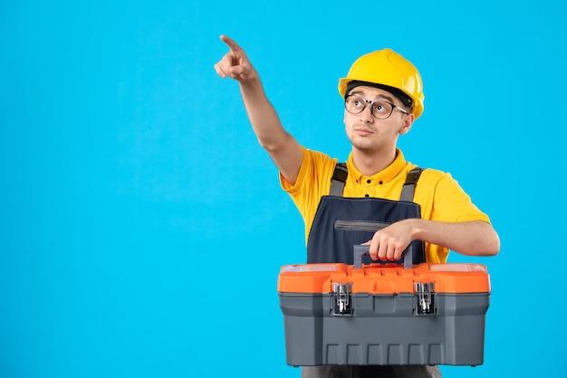Vista frontale del lavoratore maschio in uniforme gialla che indica sopra con la cassetta degli attrezzi sull'azzurro