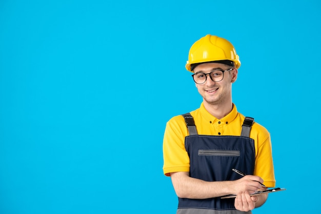 Front view male worker in yellow uniform taking notes on blue