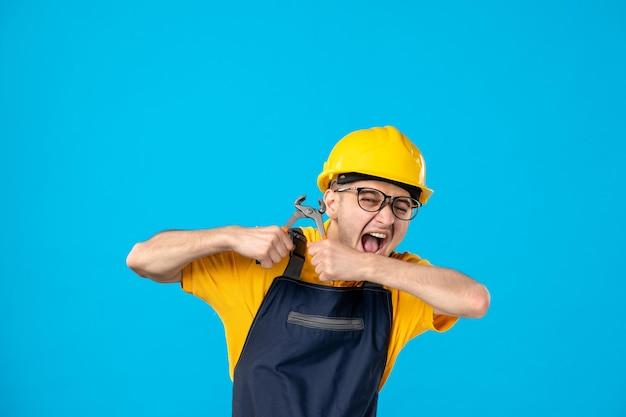 Vista frontale del lavoratore maschio in uniforme gialla che prova a rompere le pinze sull'azzurro