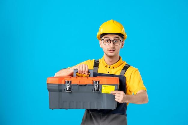 Vista frontale del lavoratore di sesso maschile in divisa gialla con carta di credito e cassetta degli attrezzi sul blu