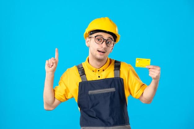 Vista frontale del lavoratore maschio in uniforme gialla con carta di credito sul blu