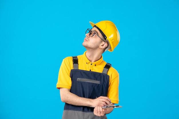 Vista frontale del lavoratore maschio in uniforme gialla con la nota di file prendere appunti sull'azzurro