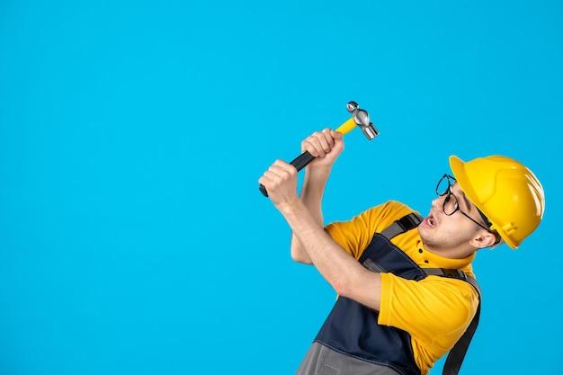 Vista frontale del lavoratore maschio in uniforme gialla con il martello su un blu