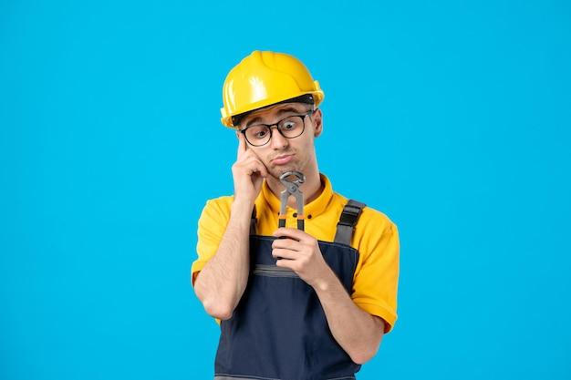 Vista frontale del lavoratore maschio in uniforme gialla con le pinze sull'azzurro