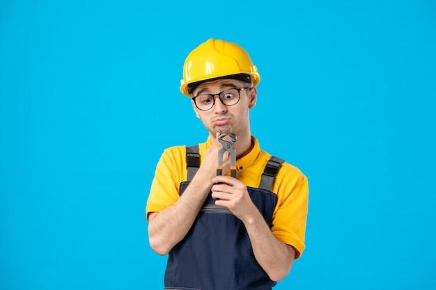 Vista frontale del lavoratore maschio in uniforme gialla con le pinze nelle sue mani sull'azzurro