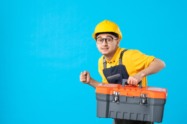Vista frontale del lavoratore di sesso maschile in uniforme gialla con cassetta degli attrezzi sul blu