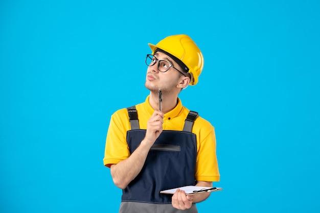 Vista frontale del lavoratore di sesso maschile nelle note di scrittura uniformi gialle sull'azzurro