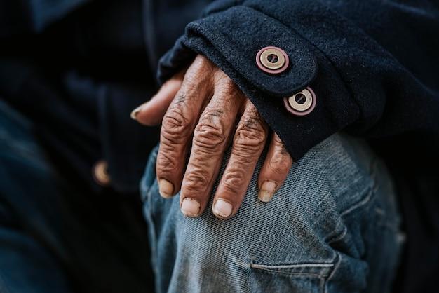 Vista frontale della mano dell'uomo senza casa malnutrito