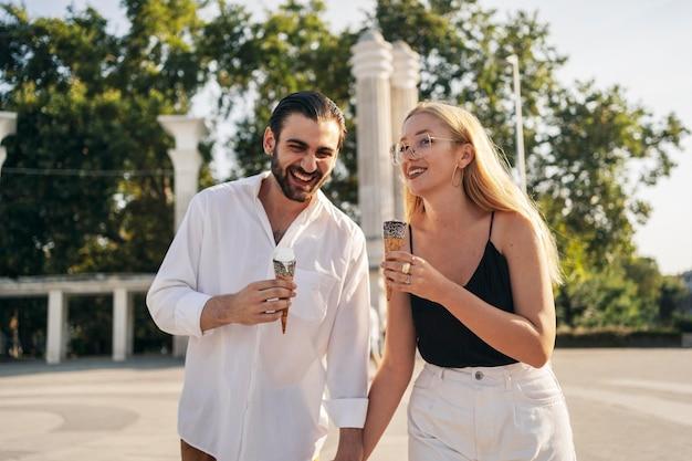 Мужчина и женщина вид спереди, наслаждаясь мороженым в парке