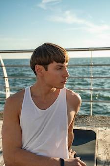 Vista frontale dell'uomo in spiaggia in canottiera