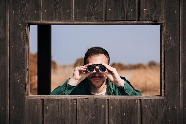 Вид спереди человек наблюдает за птицами