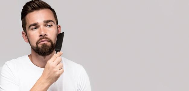 コピースペースで彼のひげを磨く正面図の男