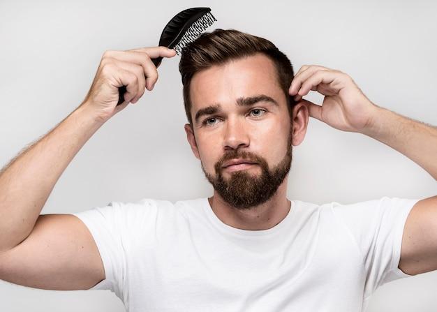 Uomo di vista frontale che spazzola i suoi capelli