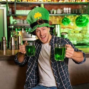 Vista frontale dell'uomo che celebra st. patrick's day al bar con bevande