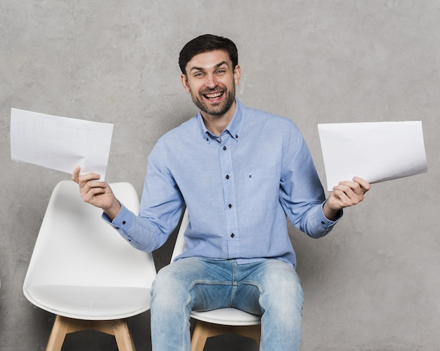 Front view of man on chair holding resumes for employment