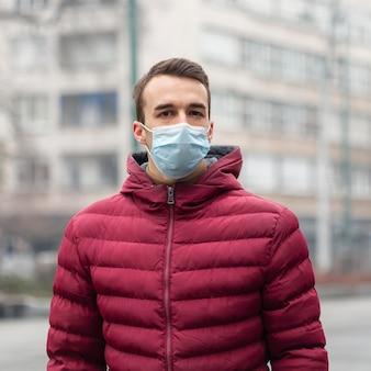 Vista frontale dell'uomo in città che indossa la mascherina medica