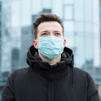 Front view of man in the city with medical mask and jacket