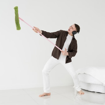 Front view of man cleaning and having fun