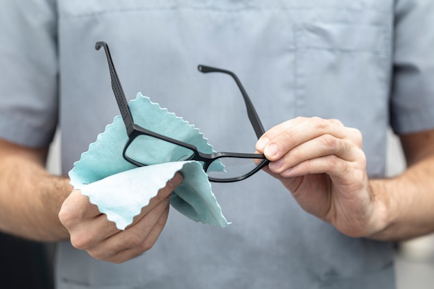 Front view of man cleaning his glasses