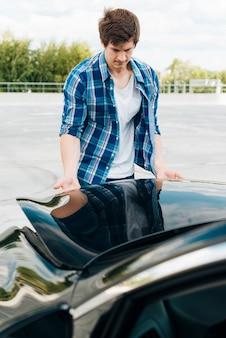 Front view of man closing car hood