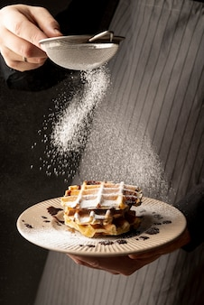 Front view of man coating waffles with powdered sugar