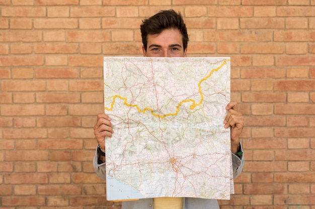 Front view man covering face with a map