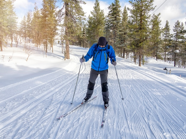 Front view of a man cross-country skiing on the trail in finland