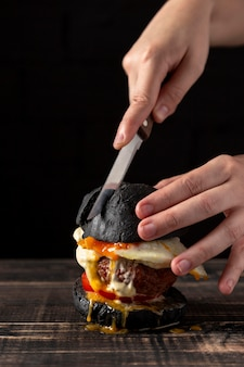 Front view man cutting burger with egg