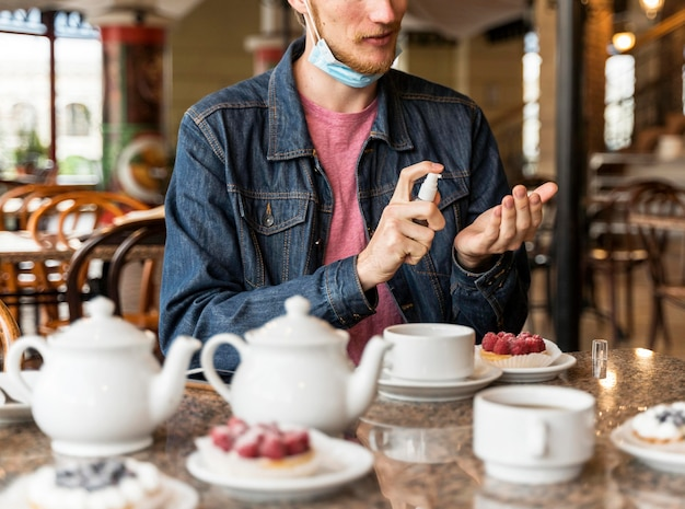 Мужчина вид спереди дезинфицирует руки в ресторане