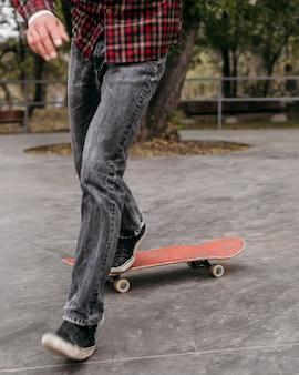 Vista frontale dell'uomo che fa i trucchi con lo skateboard fuori nel parco