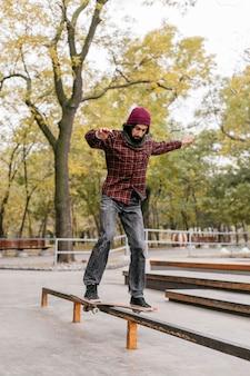 Vista frontale dell'uomo che fa i trucchi con lo skateboard all'esterno