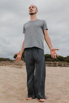 Vista frontale dell'uomo che fa yoga all'aperto