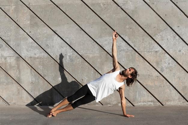 Vista frontale dell'uomo che fa yoga all'esterno