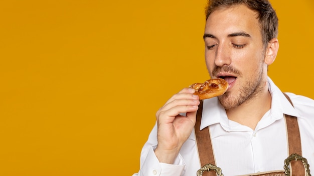 Front view of man eating german pretzel