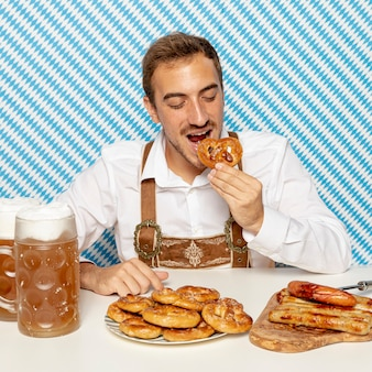 Front view of man eating german pretzels