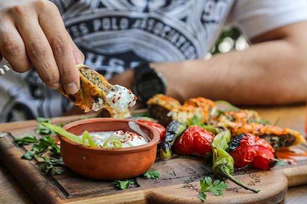 Вид спереди мужчина ест люла-кебаб в лаваше с йогуртовыми помидорами и жареным острым перцем на подносе