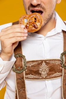 Front view of man eating pretzel