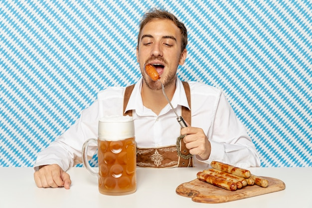 Front view of man eating sausages with beer