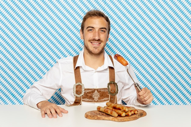 Front view of man eating sausages