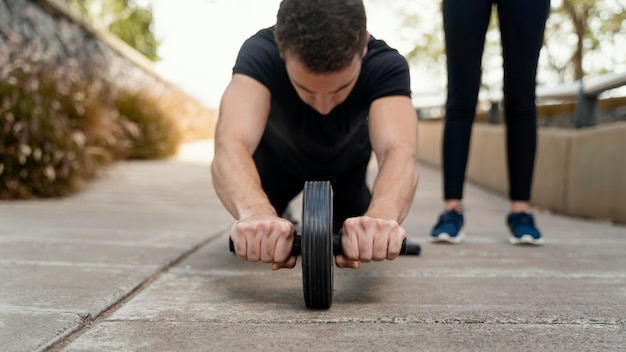 Front view of man exercising with ab wheel outside
