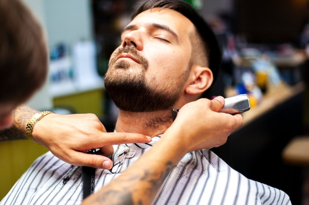 Front view man getting a beard trimmed
