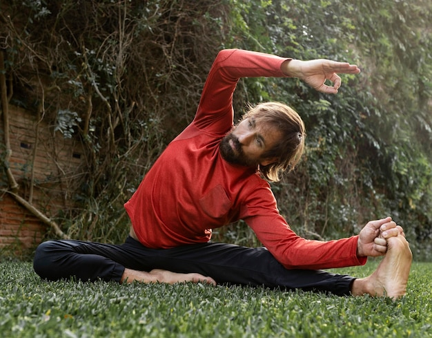 Front view of man on the grass outdoors doing yoga