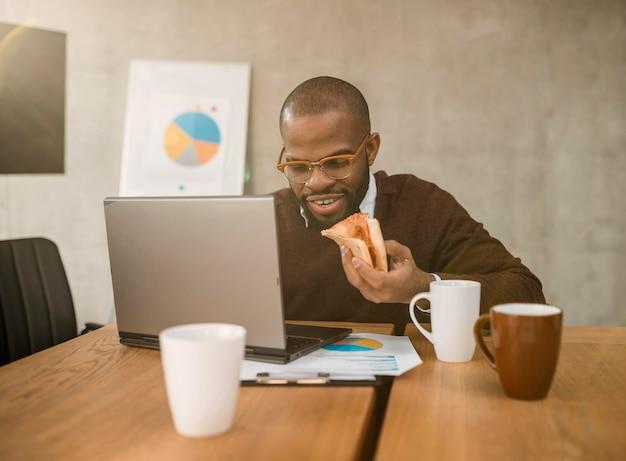 Vista frontale dell'uomo che mangia pizza durante una pausa di riunione dell'ufficio