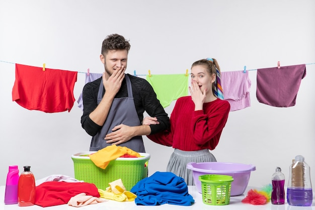 Front view of man and his wife putting theri hands on mouthes standing behind table laundry baskets and washing stuffs on table