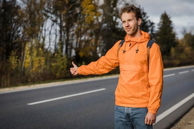 Vista frontale dell'uomo che fa l'autostop durante un viaggio su strada